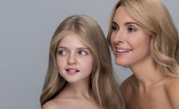Cheerful lady and her child are expressing gladness. Joyful attractive mother and her adorable little daughter are standing together with naked shoulders while royalty free stock image