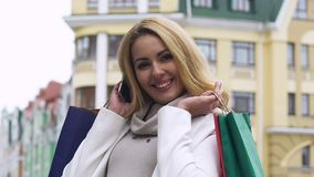 Cheerful lady holding shopping bags looking at camera, black Friday discounts. Stock footage stock video