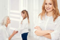Cheerful lady looking into camera with mother and daughter behind stock image