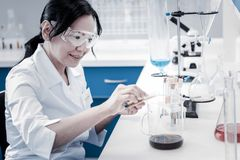 Cheerful lady pouring liquid into beaker in laboratory. Positivity is the key to success. Side view on a joyful mature scientist smiling while sitting in a lab Stock Photos