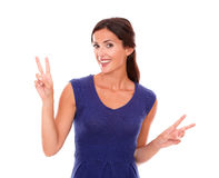 Cheerful lady in purple dress making two sign Royalty Free Stock Photography