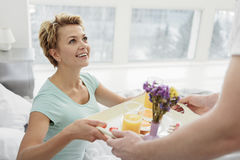 Cheerful lady receiving romantic breakfast from lover Stock Photo
