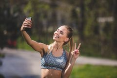 Cheerful lady is shooting herself with phone outdoors stock photo