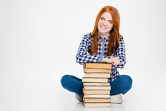 Cheerful lady sitting and leaning on stack of books Stock Image