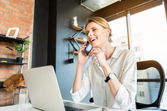 Cheerful lady sitting at table with mobile phone Royalty Free Stock Photo