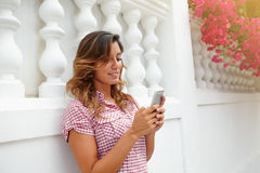 Cheerful lady smiling while using smart phone Stock Photography