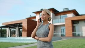 Cheerful lady talking mobile at luxury villa. Portrait of pretty girl with phone stock video
