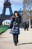 Cheerful lady walking by the Eiffel tower Royalty Free Stock Photography