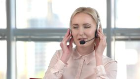 Cheerful lady working in call center. Business woman is talking with someone using headset, huge bright windows background stock footage
