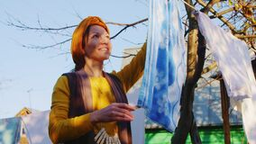 Cheerful lady in yellow hangs clean blue towel on rope