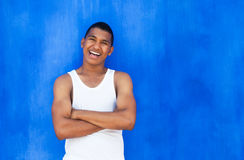 Cheerful latin guy in front of a blue wall Stock Photo