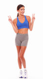 Cheerful latin lady standing looking at you. Cheerful latin lady in sport clothing standing against white background - copyspace Stock Photo