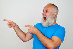 Cheerful laughing aged man looking and pointing to his right Royalty Free Stock Photography