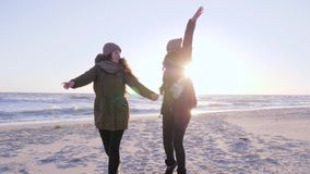 Cheerful leisure, youth running around and waving hands at beach in sun beams. Cheerful leisure, youth running around and waving hands at beach in bright sun stock footage