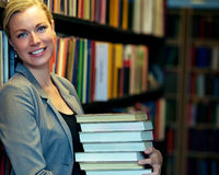 Cheerful librarian or student. Standing inside a library carrying a stack of large books either for education and research or inventory that has to be replaced Stock Photos