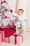 Cheerful little baby boy playing near the Christmas tree Royalty Free Stock Photo