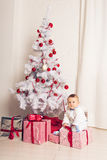 Cheerful little baby boy playing near the Christmas tree Stock Images