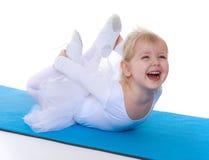 Cheerful little ballerina lays on the mat sport Royalty Free Stock Image