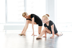 Cheerful little ballerina and teacher stretching in ballet school stock image