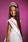 Cheerful little beauty winner posing with tiara Stock Photos