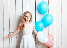 Cheerful little blonde girl with balloons on white wood backgrou Stock Photography