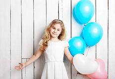 Cheerful little blonde girl with balloons on white wood backgrou Royalty Free Stock Photo