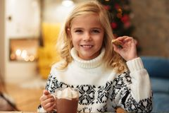 Cheerful little blonde girl drinking cacao with marshmallow hold. Ing cookie on Christmas morning, looking at camera Royalty Free Stock Photo