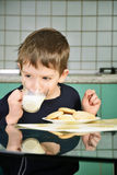 Cheerful little boy drinking milk, sitting at the dinner table. Stock Photos
