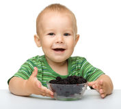 Cheerful little boy is eating blackberry Royalty Free Stock Images