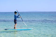 Kid at vacation. Cheerful little boy enjoying stand up paddleboarding alone, active vacation concept, copy space on right Royalty Free Stock Images
