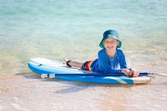 Kid at vacation. Cheerful little boy enjoying stand up paddleboarding alone, active vacation concept Royalty Free Stock Photography