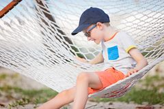Kid at vacation. Cheerful little boy enjoying tropical vacation in hammock Stock Image