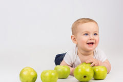 Cheerful little boy with green apple. Is smiling while lying on a floor Royalty Free Stock Images