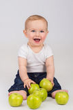 Cheerful little boy with green apple is smiling. While sitting on a floor Stock Photography
