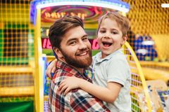 Cheerful little boy having fun with his dad. At the entertainment centre royalty free stock image