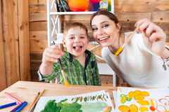 Cheerful little boy and his mother showing paintbrushes to camera Royalty Free Stock Photos