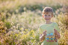 Boy at easter time. Cheerful little boy holding basket full of easter eggs after egg hunt at beautiful blooming field at spring time Royalty Free Stock Photos