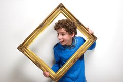 Cheerful little boy holding picture frame Royalty Free Stock Image