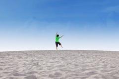Cheerful little boy jump on desert Stock Image