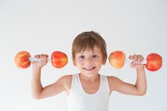 Cheerful little boy lifts weights made from apples. Cheerful smiling little boy lifting weights made from apples Stock Photography