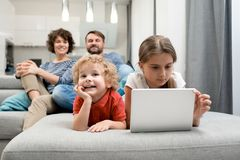 Enjoying Weekend at Home. Cheerful little boy lying on cozy sofa and watch educational program with his parents while his elder sister wrapped up in playing Stock Photos