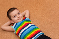 Cheerful little boy lying on the floor Stock Photo