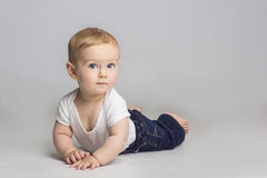 Cheerful little boy while lying on a floor. In studio Royalty Free Stock Images