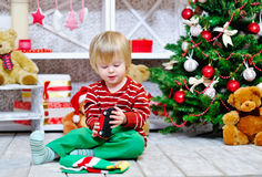 Cheerful little boy playing with his red toy car Stock Images