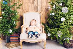 Cheerful little boy playing with his toy by the Christmas tree Stock Images
