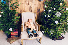 Cheerful little boy playing with his toy by the Christmas tree Stock Photography