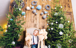 Cheerful little boy playing with his toy by the Christmas tree Royalty Free Stock Photos