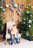 Cheerful little boy playing with his toy by the Christmas tree Royalty Free Stock Images