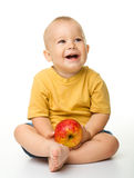 Cheerful little boy with red apple Stock Photography