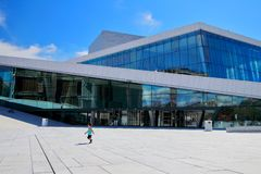 Cheerful little boy runs in front of the Oslo opera building during a sunny summer morning, Oslo, Norway royalty free stock image